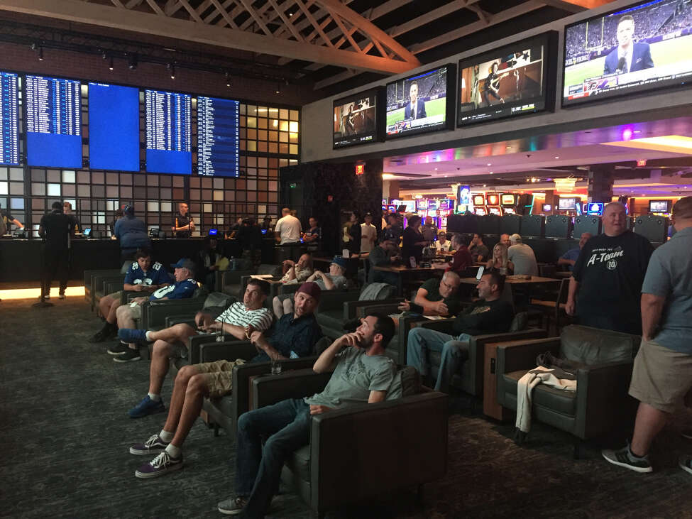 Gamblers watch the NFL pre-game shows in the Rivers Casino and Resorts' sportsbook lounge.