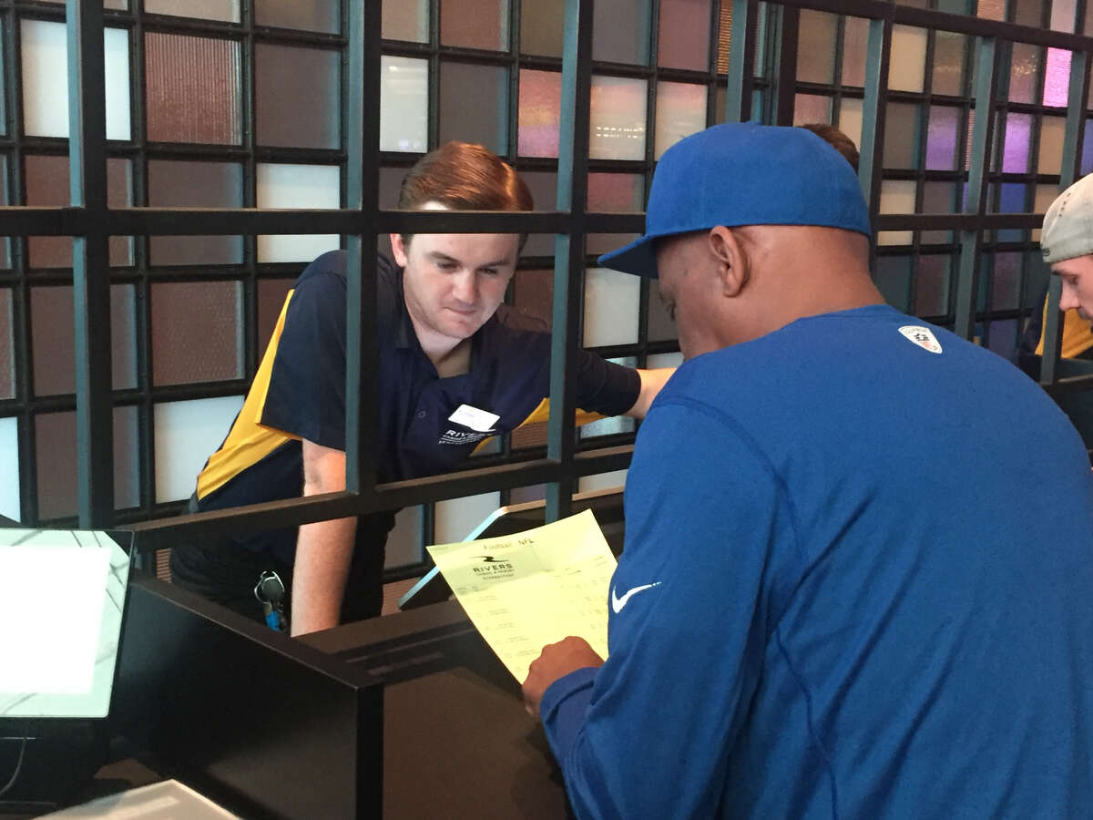 A Rivers Casino and Resort employee helps a customers place a bet Sunday before the NFL action begins.