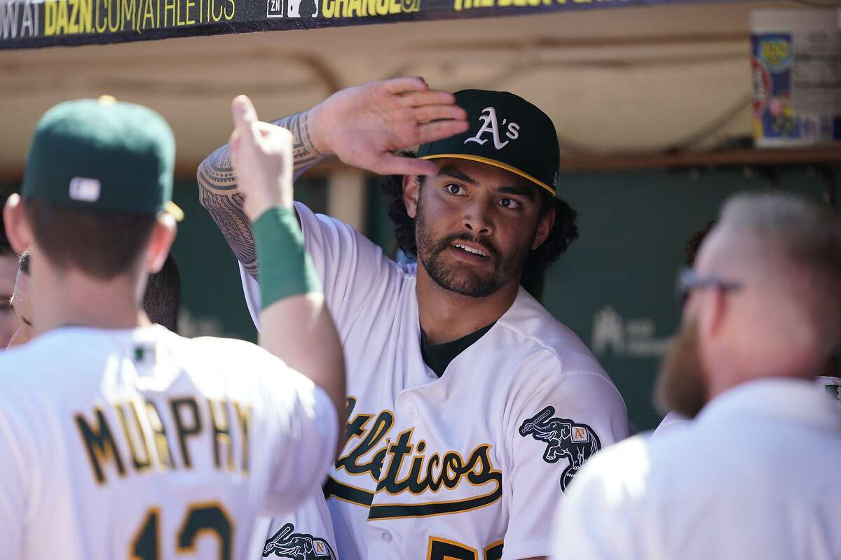 Oakland Athletics pitcher Sean Manaea, center, high-fives teammates in the dugout after being taken out during the seventh inning of a baseball game against the Detroit Tigers, Sunday, Sept. 8, 2019, in Oakland, Calif. (AP Photo/Tony Avelar)