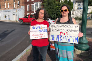 Miriam Axel-Lute, 44, and Brianna Becker, 38, hold up signs at an ICE protest in Troy on Sunday, Sept. 8, 2019.