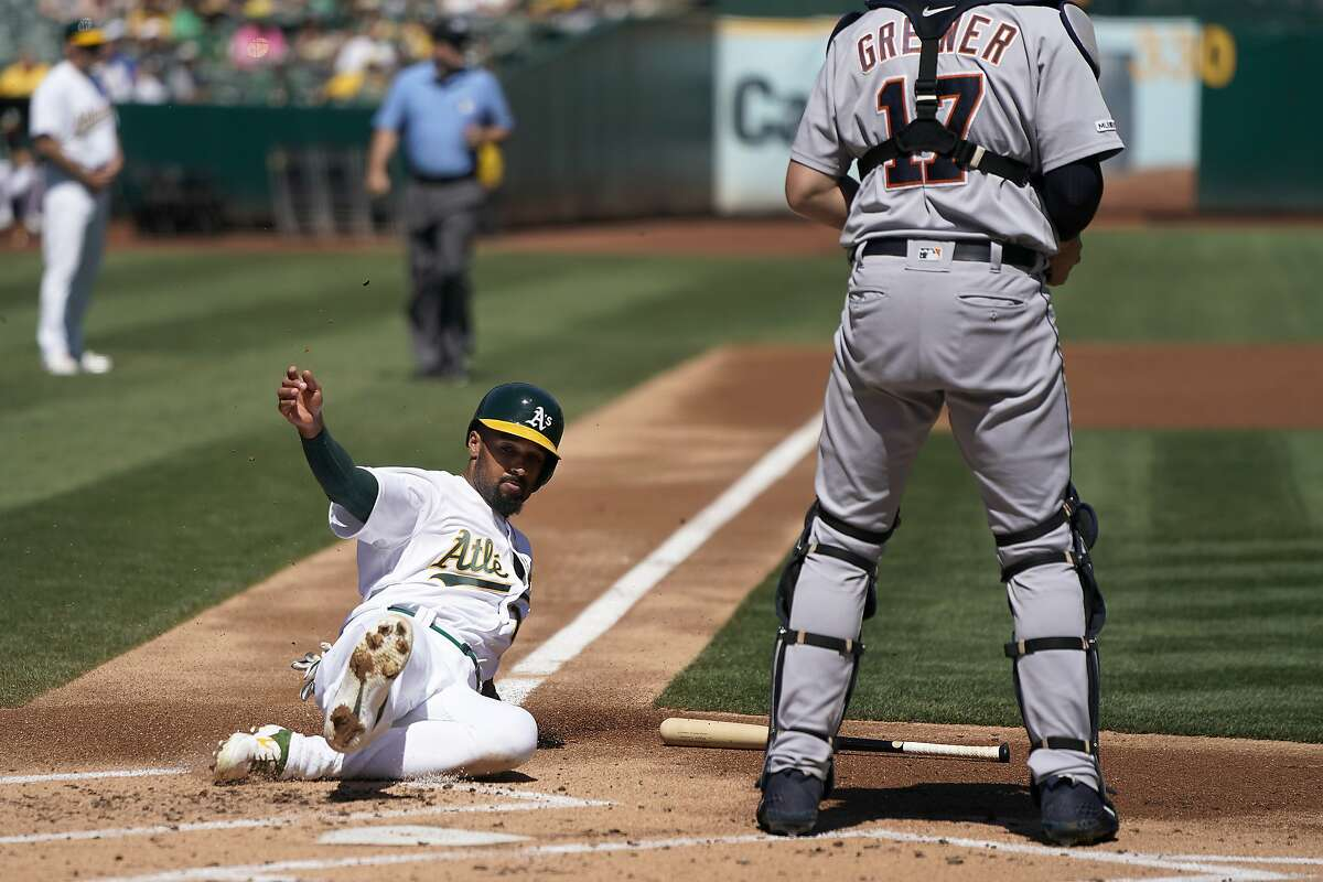 Oakland Athletics' Marcus Semien, left, slides into home plate to score past Detroit Tigers catcher Grayson Greiner (17) on a ground ball by Mark Canha during the first inning of a baseball game Sunday, Sept. 8, 2019, in Oakland, Calif. (AP Photo/Ben Margot)