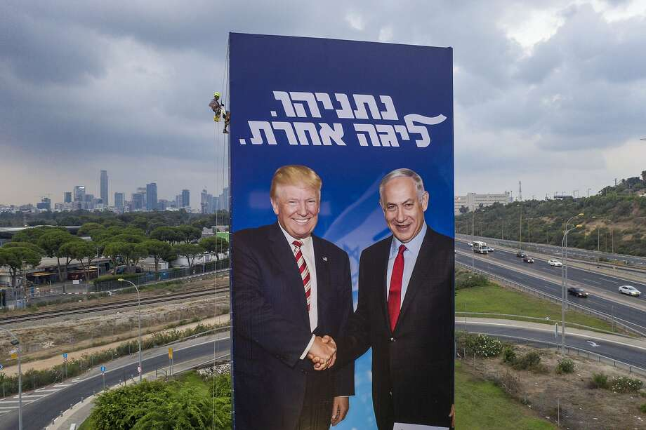 A worker hangs a campaign billboard showing Israeli Prime Minister Benjamin Netanyahu with President Trump, an ardent supporter, in Tel Aviv. The repeat election is set for Sept. 17. Photo: Oded Balilty / Associated Press