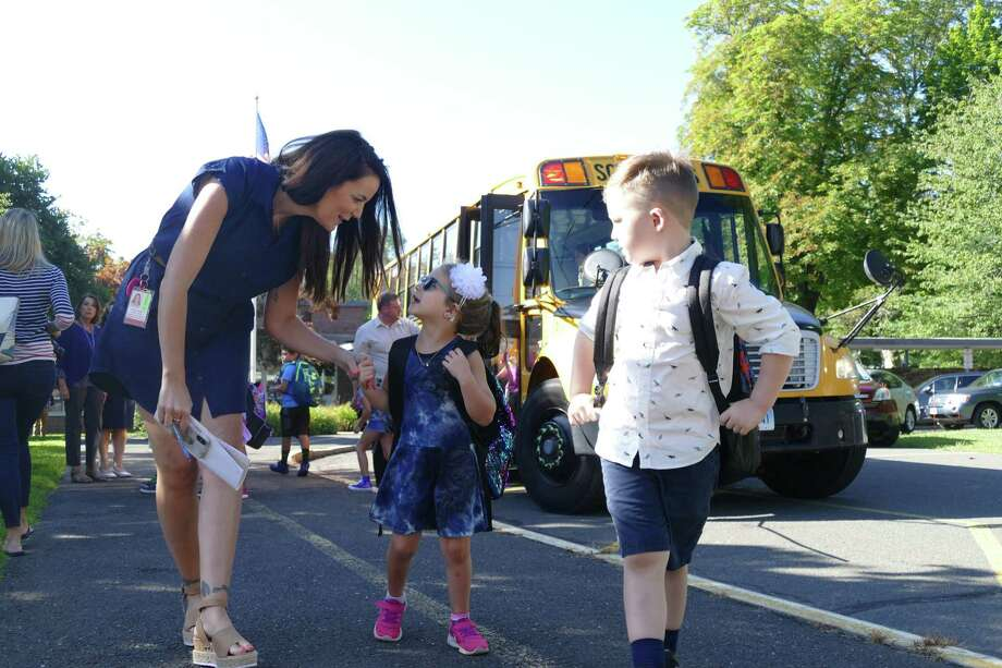 Veterans Park teacher Kelly Feeney leads two kindergarten students to their rooms on the first day of school. Photo: Stephen Coulter / Hearst Connecticut Media