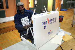 Everett Taylor prepares a polling booth in preparation for Tuesday's primary election at Barnum School, in Bridgeport, Conn. Sept. 9, 2019.