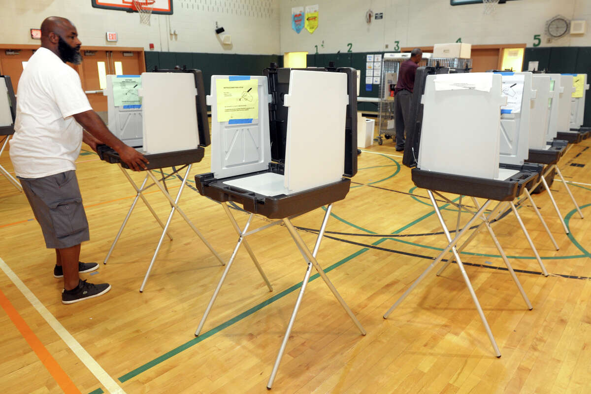 Scott Lawrence arranges polling booths in preparation for Tuesday's primary election at Barnum School, in Bridgeport, Conn. Sept. 9. 2019.