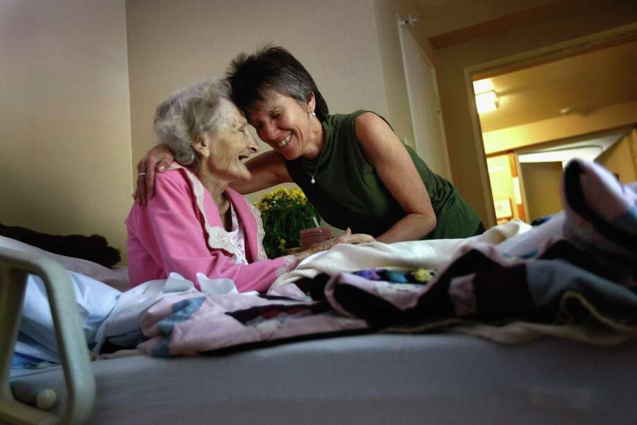 A massage therapist embraces a terminally ill patient following her body treatment. Photo: John Moore / Getty Images / Getty Images North America