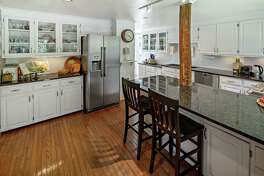 The updated kitchen features granite counters, a breakfast bar, an exposed beam, and stainless appliances.