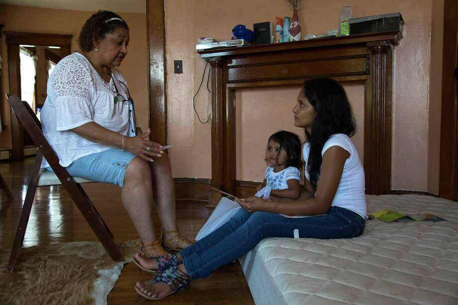 A community health worker in Bridgeport, Conn., discusses vaccines with a client.  These workers reach those who cannot afford care. Photo: Connecticut Post File Photo