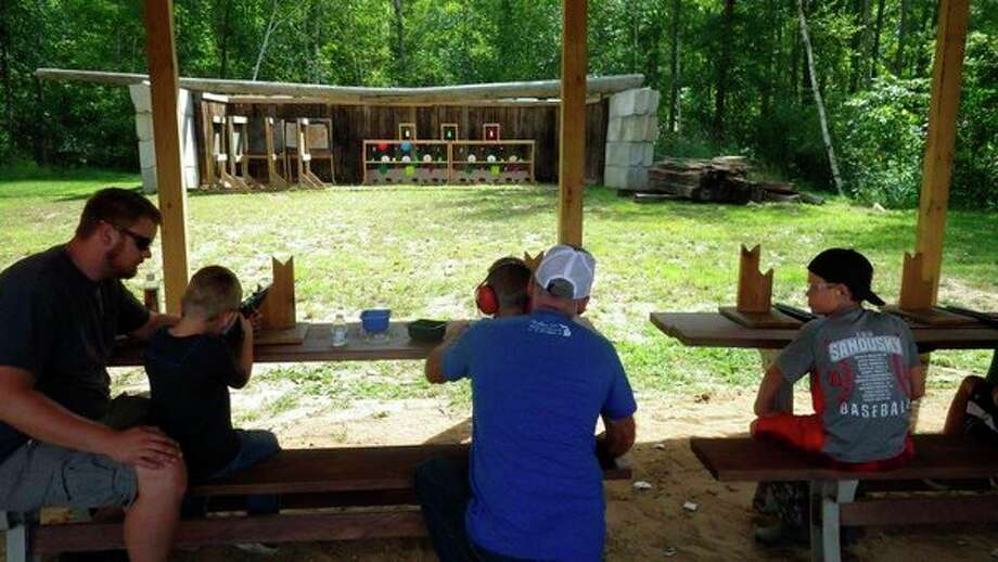 Adults carefully mentor kids on the .22 rifle range at the Cass City Gun Club's recent Free Youth Day. (Tom Lounsbury/Hearst Michigan)