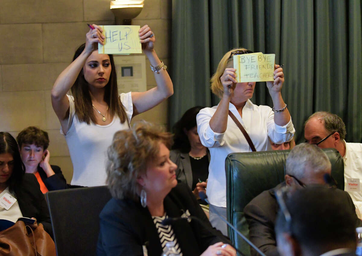 Two mothers who are against the mandatory vaccination of children, Melissa Bordes, left, from Mineola, and Rita Palma from Blue Point, hold up hand-written signs during the Board of Regents meeting at the State Education Department on Monday, Sept. 9, 2019, in Albany, N.Y. Hundreds of families came to Albany on Monday to pressure the Board of Regents to delay the implementation of a law that ends religious exemptions to New York school vaccination requirements. Children who are not vaccinated will not be allowed to stay in private or public schools. (Paul Buckowski/Times Union)