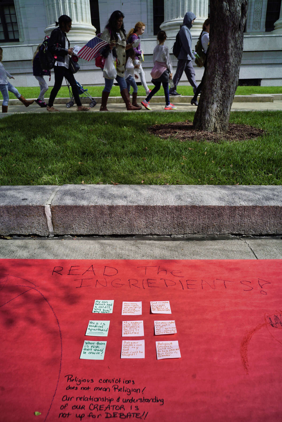 Families opposed to vaccinating their children walk past a scroll laid out on the ground that families wrote on, outside the New York State Education building on Monday, Sept. 9, 2019, in Albany, N.Y. Families came to Albany to pressure the Board of Regents to delay the implementation of a law that ends religious exemptions to New York school vaccination requirements. (Paul Buckowski/Times)