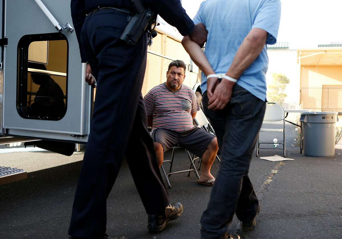After being arrested on suspicion of soliciting an undercover officer posing as a prostitute, Gabriel Moreno sits at the Richmond Police Department command center on 22nd Street as fellow arrestee Rogelio Gutierrez arrives during a sting operation in Richmond, Calif. on Thursday, September 4, 2014.