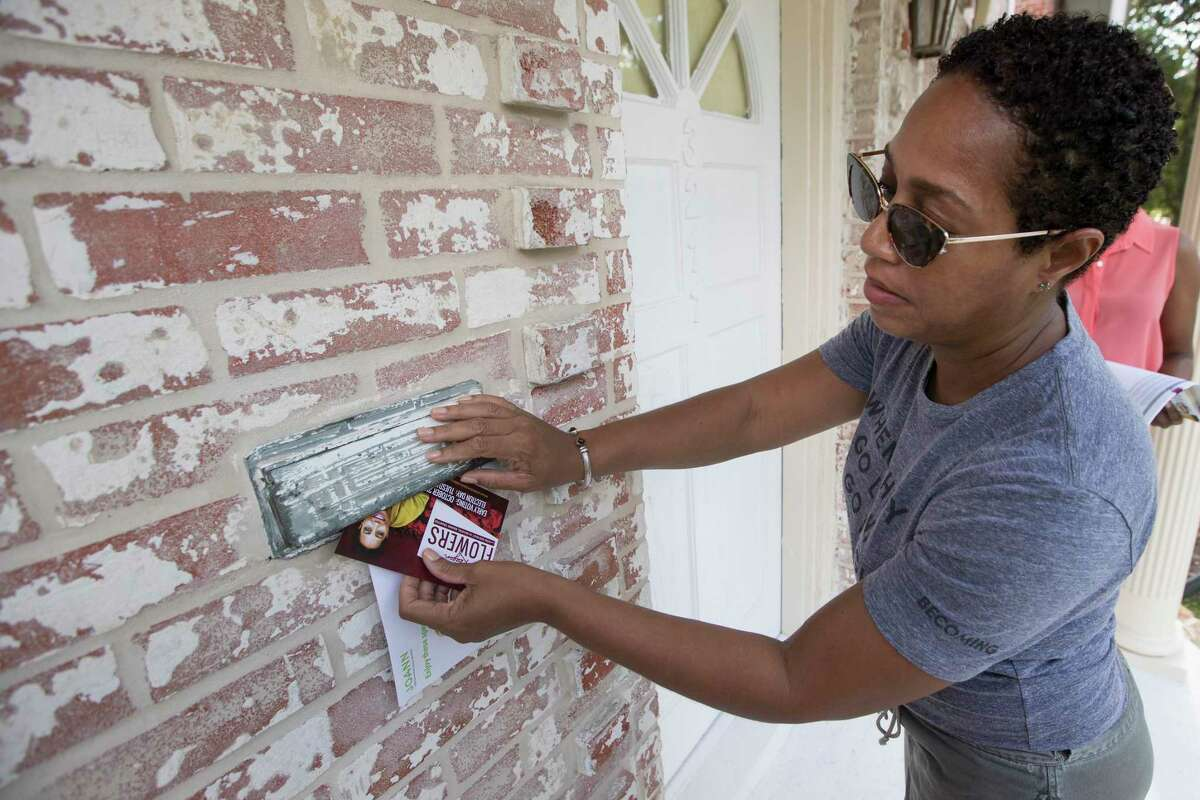 Dr. Reagan Flowers places a campaign card in a mailbox as she walks through a neighborhood campaigning for a seat on the Houston ISD school board on Saturday, Sept. 7, 2019, in Houston. Flowers is one of four candidates running to replace outgoing District IV Trustee Jolanda Jones
