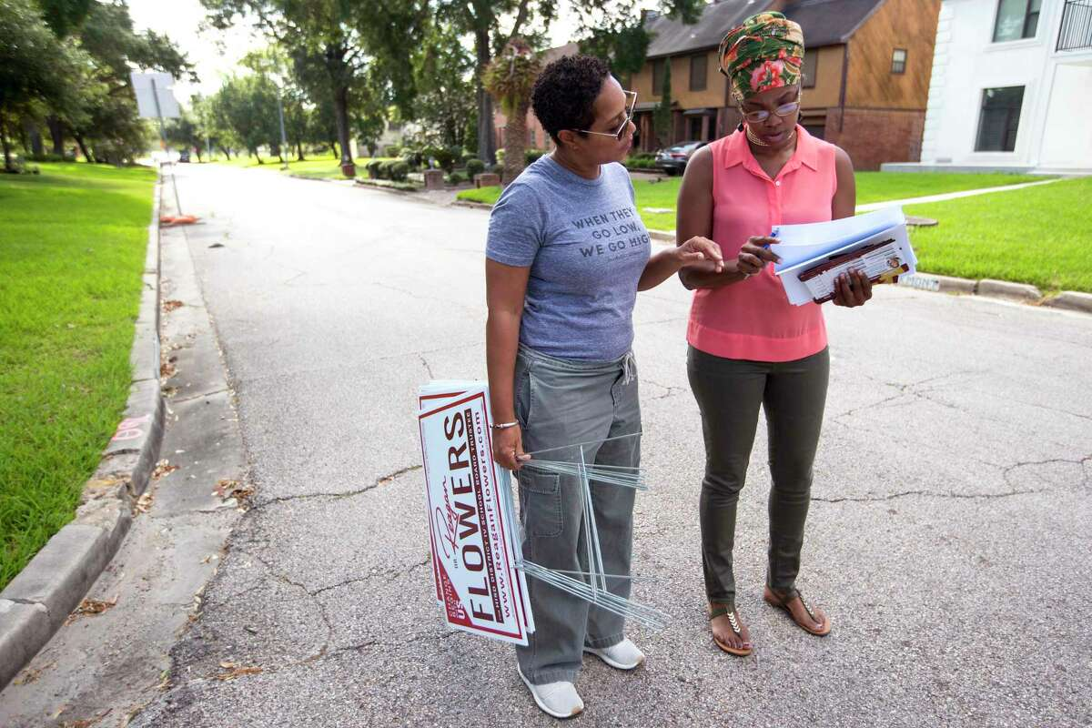 Dr. Reagan Flowers, left, and volunteer L.J. Garfield walk through a neighborhood as she campaigns for a seat on the Houston ISD school board on Saturday, Sept. 7, 2019, in Houston. Flowers is one of four candidates running to replace outgoing District IV Trustee Jolanda Jones