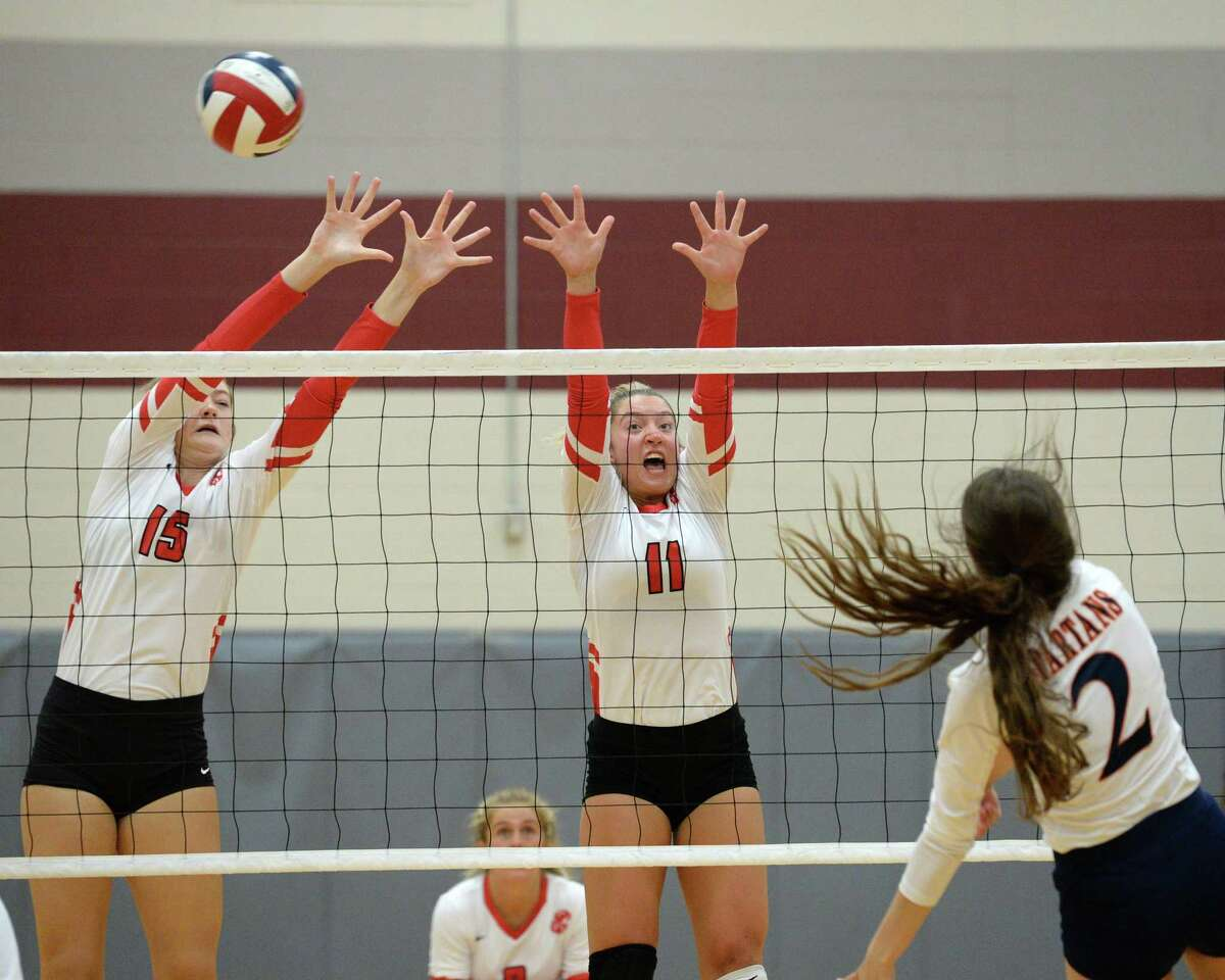 Jordan Gamble (15) and Hannah Hoover (11) of Katy attempt to block a shot by Gabrielle Collins (2) of Seven Lakes during the second set of a volleyball match between the Seven Lakes Spartans and the Katy Tigers on Friday, August 9, 2019 at Cinco Ranch HS, Katy, TX.