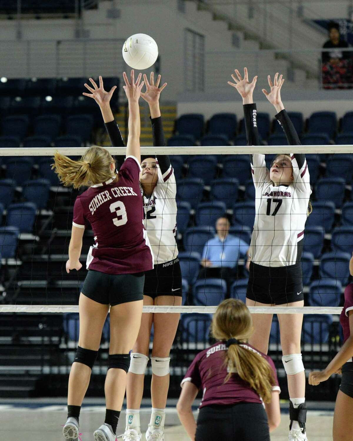 McKay Wilson (3) of Summer Creek attempts a kill shot as Logan Lednicky (12) and Avery Shimaitis (17) of George Ranch go for a block in the first set of a Class 6A Region III Area-round playoff volleyball match between the George Ranch Longhorns vs Summer Creek Bulldogs on Friday, November 2, 2018 at Delmar Fieldhouse, Houston, TX.