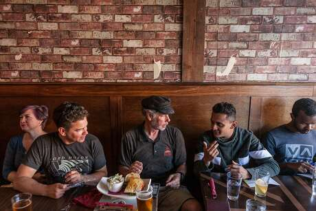 Cheryl Blain (left), Marc Igel, Mark Stanley, Shivam Patel and Jordan Duprey talk about the day's dive adventures over food and drink at Monterey's Bulldog Pub. Photo: Brian Feulner / Special To The Chronicle