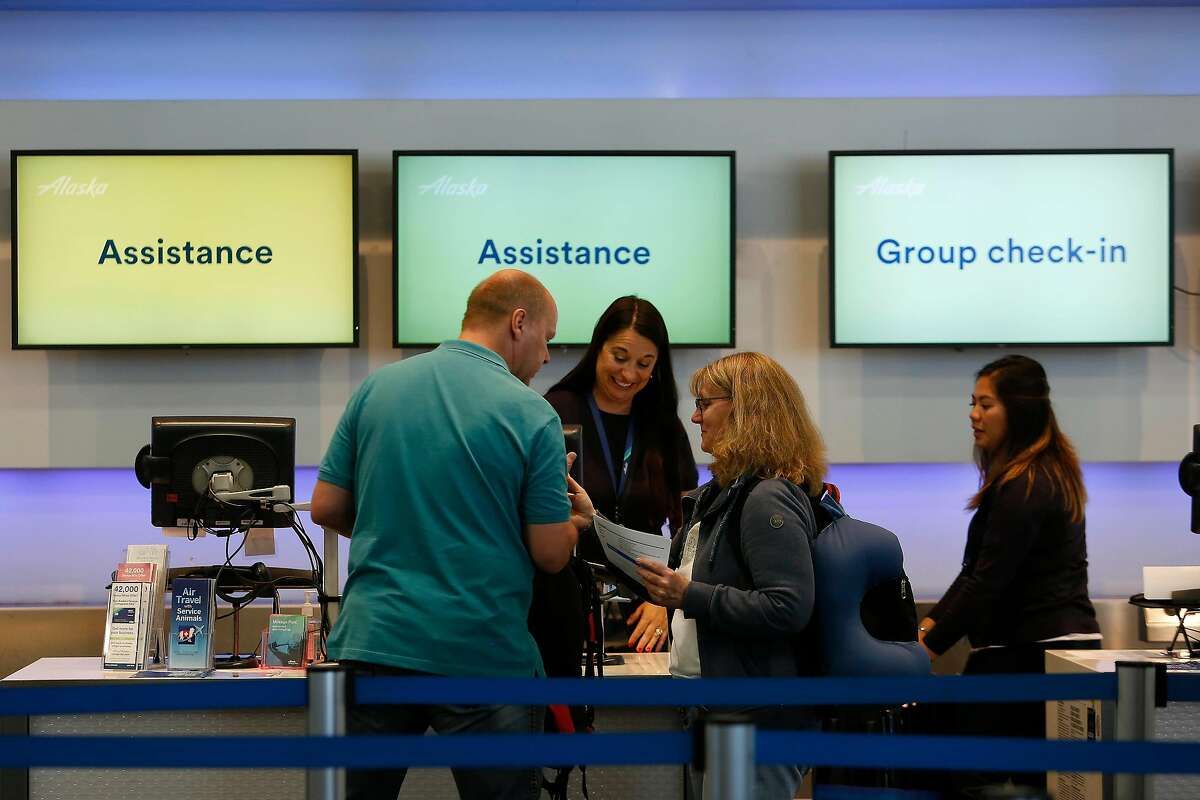 Andre Schultz (l to r) and Bettina Schutz, both of Germany, are helped at a ticketing counter at San Francisco International Airport on Monday, September 9, 2019 at SFO in San Francisco, CA.