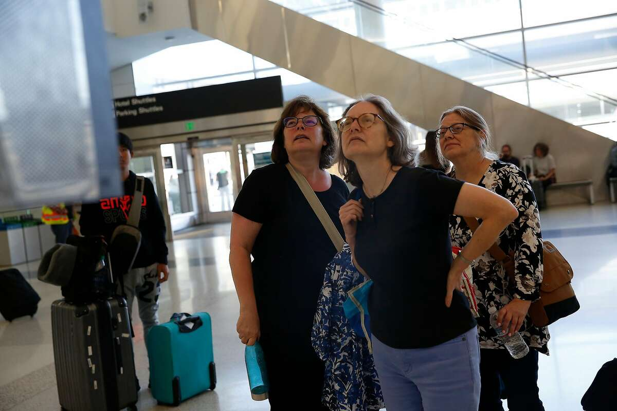 Betsy Curlin of Illinois (l to r) , Karen Kramer of Massachusettes and Shirley Kramer of Illinois study a departure and arrivals board at San Francisco International Airport on Monday, September 9, 2019 at SFO in San Francisco, CA. Curlin and Shirley Kramer said their flight times had been bounced around as it had been moved up and then back.