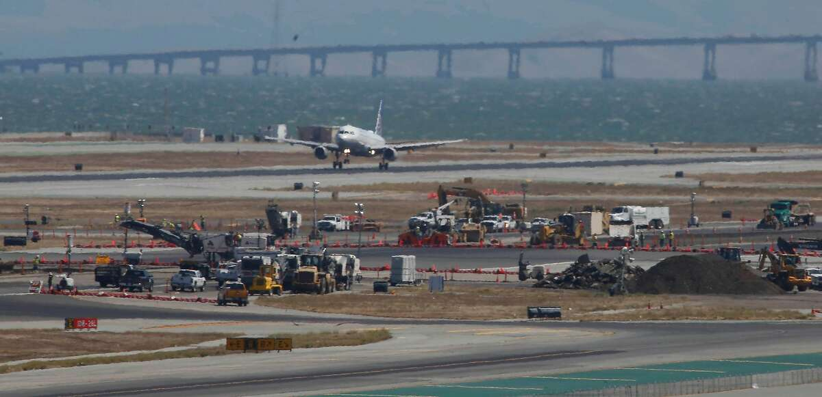 An airplane is seen landing next to construction equipment on a runway at San Francisco International Airport on Monday, September 9, 2019 at SFO in San Francisco, CA.