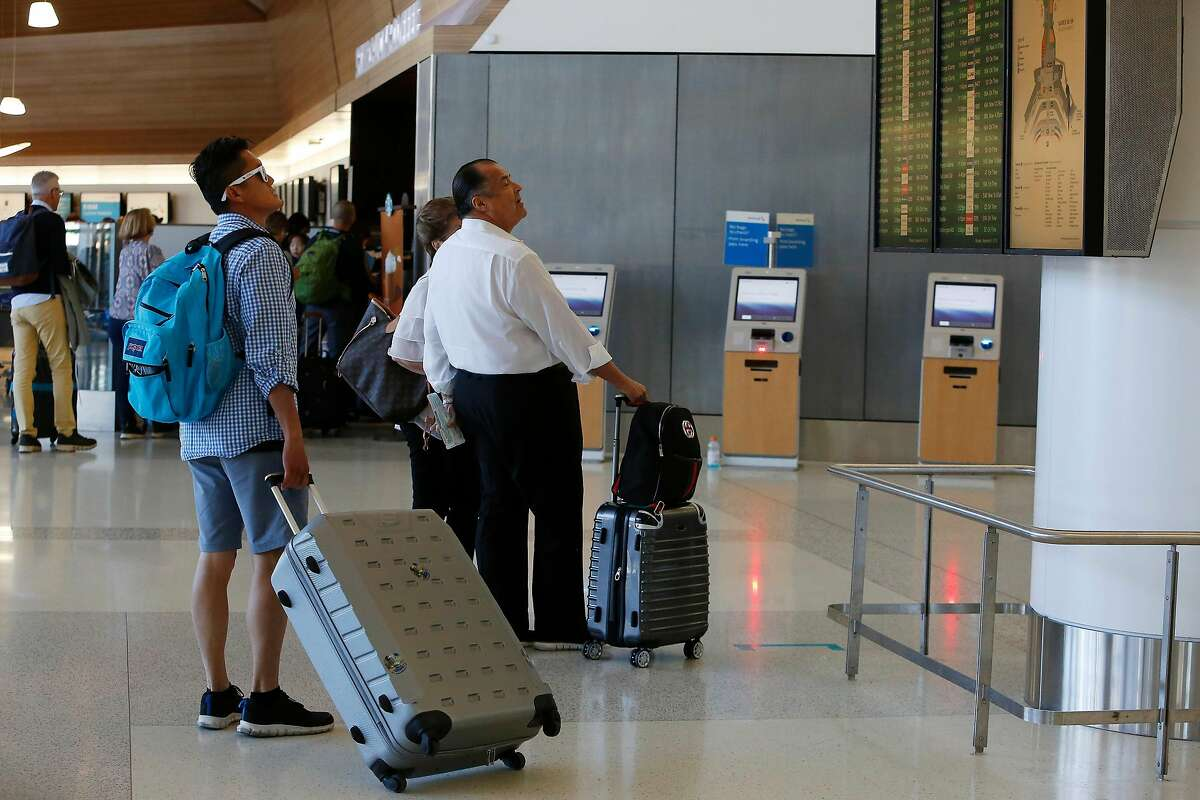People look at arrival and departure display boards at San Francisco International Airport on Monday, September 9, 2019 at SFO in San Francisco, CA.