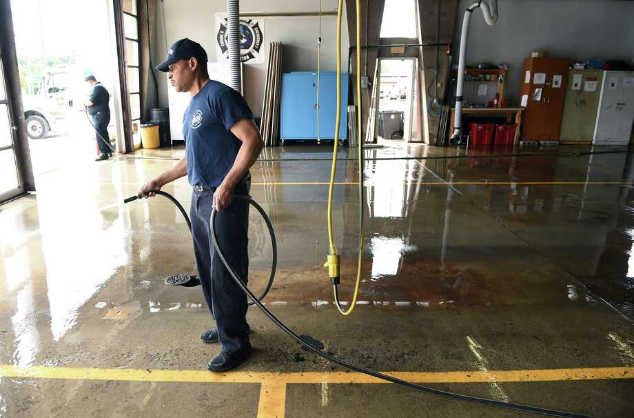Firefighters Theodore Oliver and Jonathan Kendall(background) clean the floor of Engine #5 Woodward Station in New Haven on Sept. 9, 2019 where primary voting will take place. Photo: Arnold Gold / Hearst Connecticut Media / New Haven Register