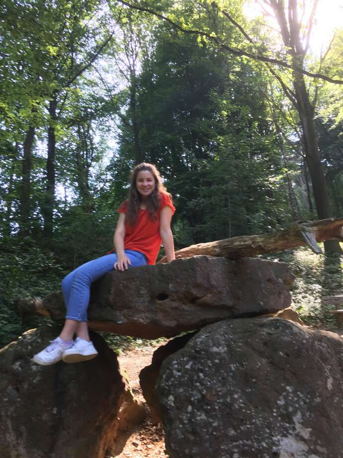 Trinity School senior Vivienne Dragun sits atop a rock in the woods near Kortrijk, Belgium. Dragun spent a month in Belgium on a Lions Club Youth Exchange program. Photo: Courtesy Photo