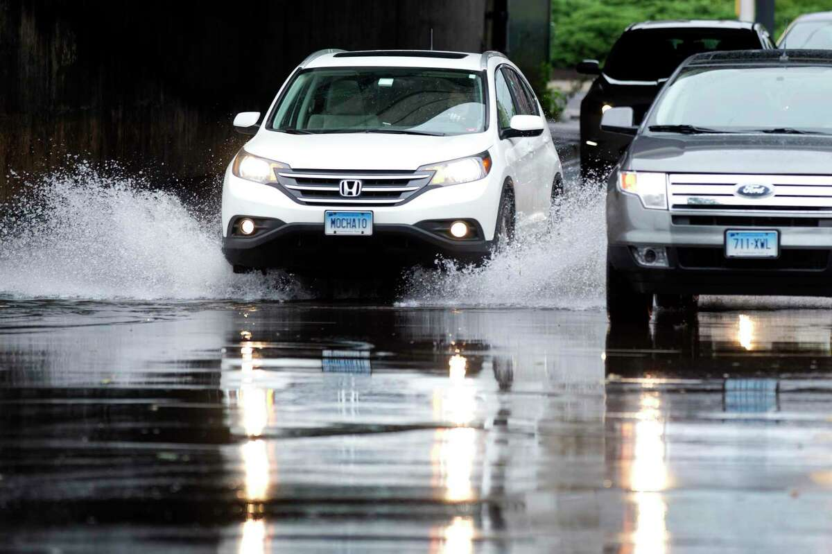 Cars drive through a puddle following a rain storm at Canal Street and North State Street in Stamford.