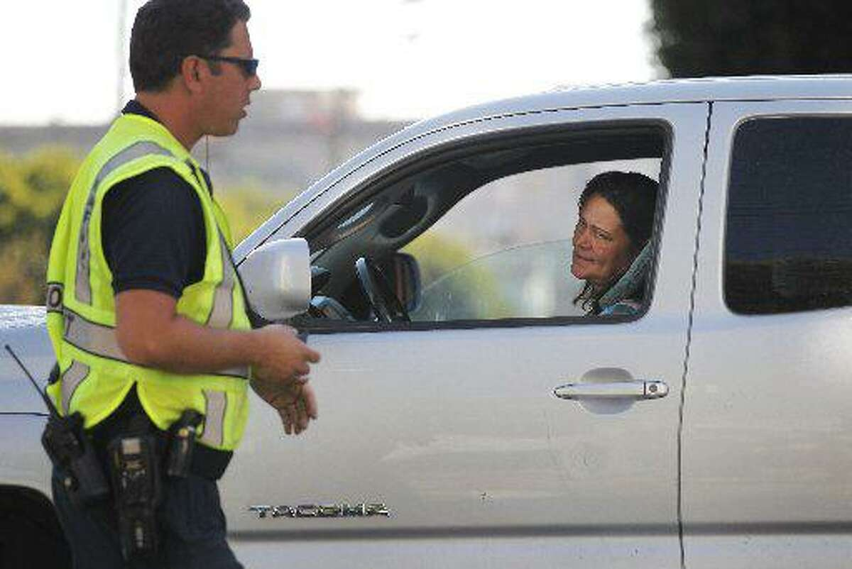 """A woman reacts after SFMTA officer only identified for safety reasons as badge number 57, tells her not to go into the intersection at 2nd and Bryant Streets as part of San Francisco Municipal Transportation Agency's (SFMTA) testing of """"Don't Block the Box"""" enforcement program at two SOMA intersections Sept. 11, 2014 in San Francisco, Calif."""