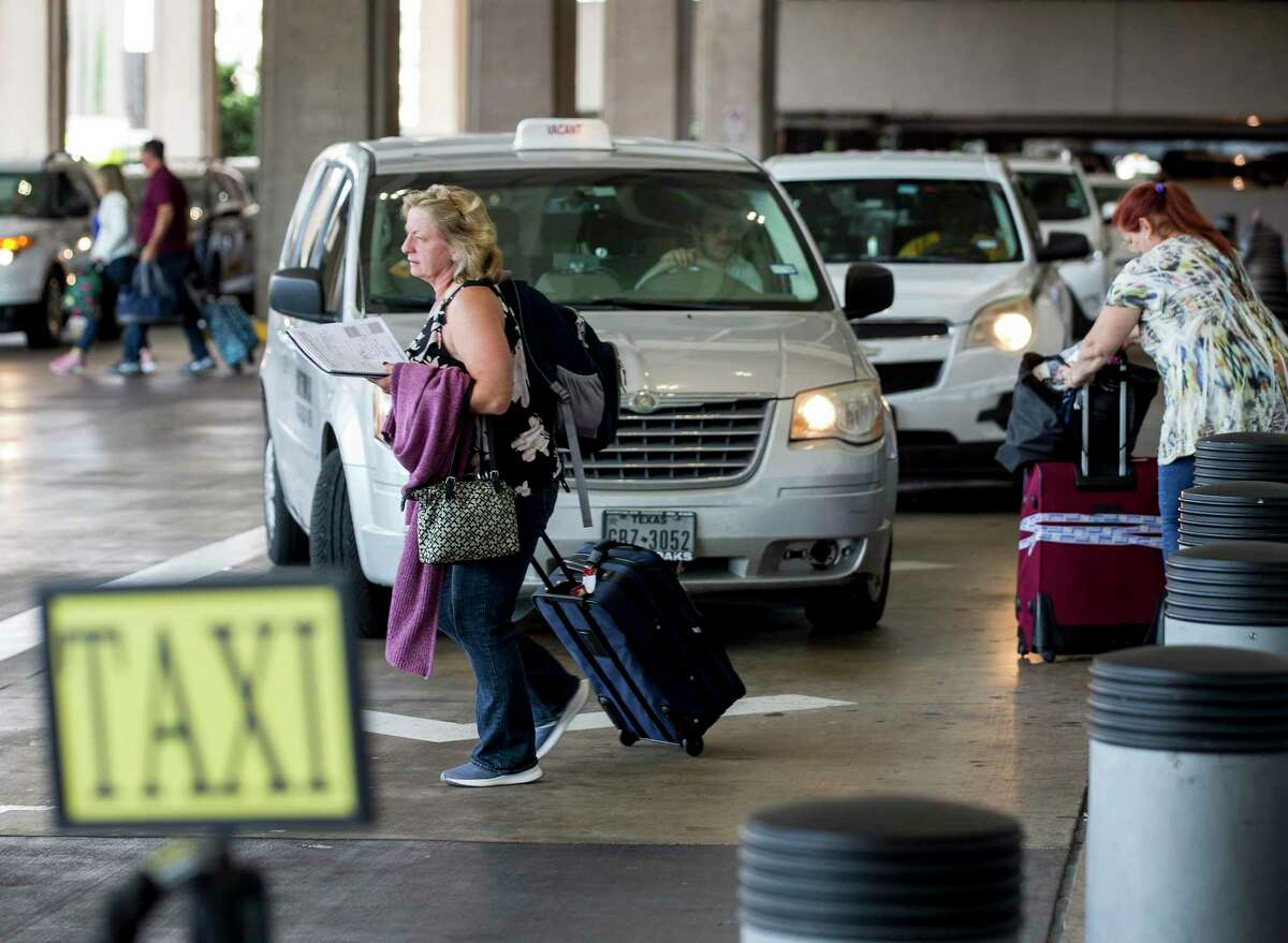 Taxi drivers wait for fares outside George Bush Intercontinental Airport on Friday, Sept. 6, 2019, in Houston. Houston taxi drivers will face lower fees and fewer regulations under a plan approved by City Council. The new rules come as taxi companies struggle to stay financially afloat amid increased competition from ride-sharing companies such as Lyft and Uber. Under the plan, the city will lower taxi permit fees from $580 to $450, and create a three-time lottery system through which almost 900 new permits will be issued by 2020.