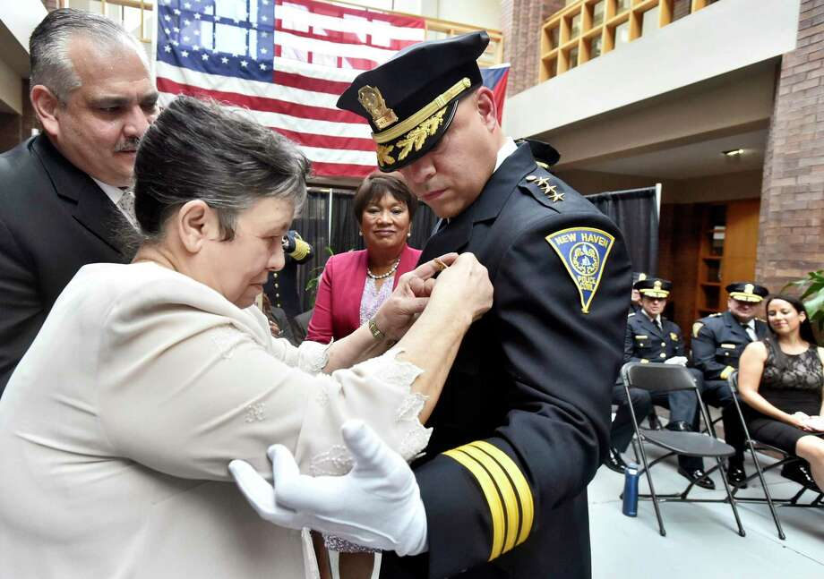 New Haven Police Chief Otoniel Reyes has his badge pinned by his mother, Damaris Reyes of New Haven, as Pator Abraham Colon of New Haven, left, New Haven Mayor Toni Harp, center, and his wife, Leslie, far right, watch during the swearing-in ceremony Monday afternoon at New Haven City Hall. Photo: Peter Hvizdak / Hearst Connecticut Media / New Haven Register