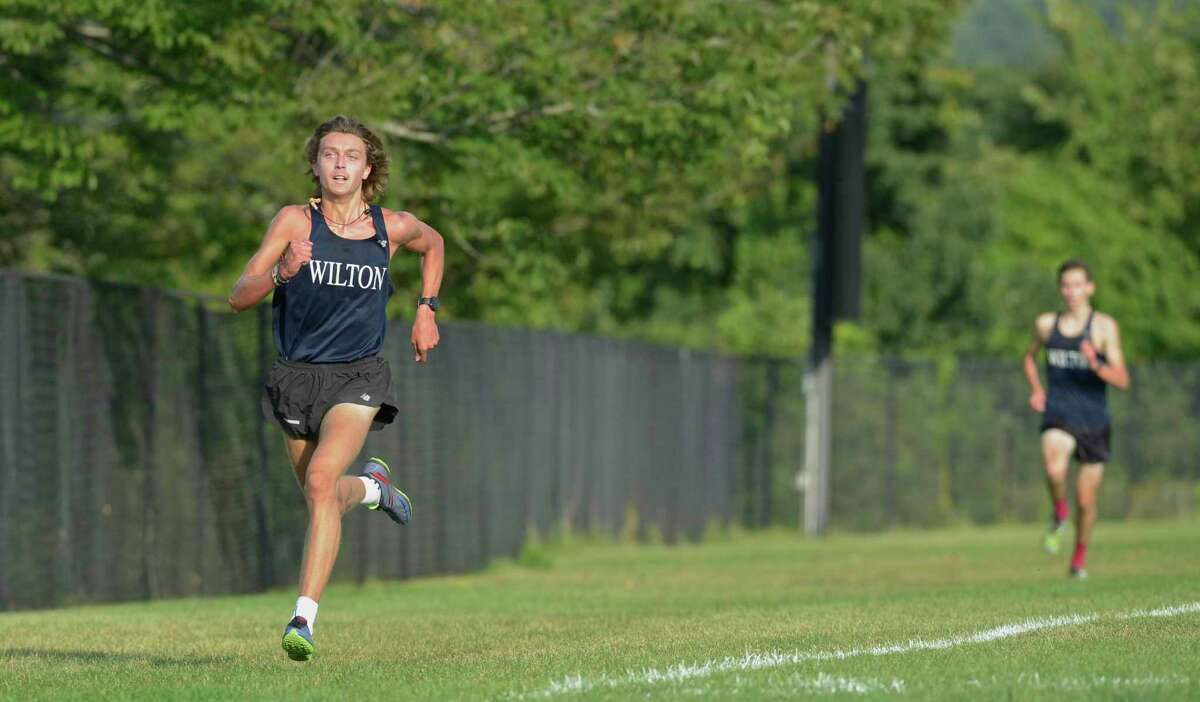 Wilton's Davis Cote, left, competes at against Ridgefield, Stamford and Warde on Sept. 9.