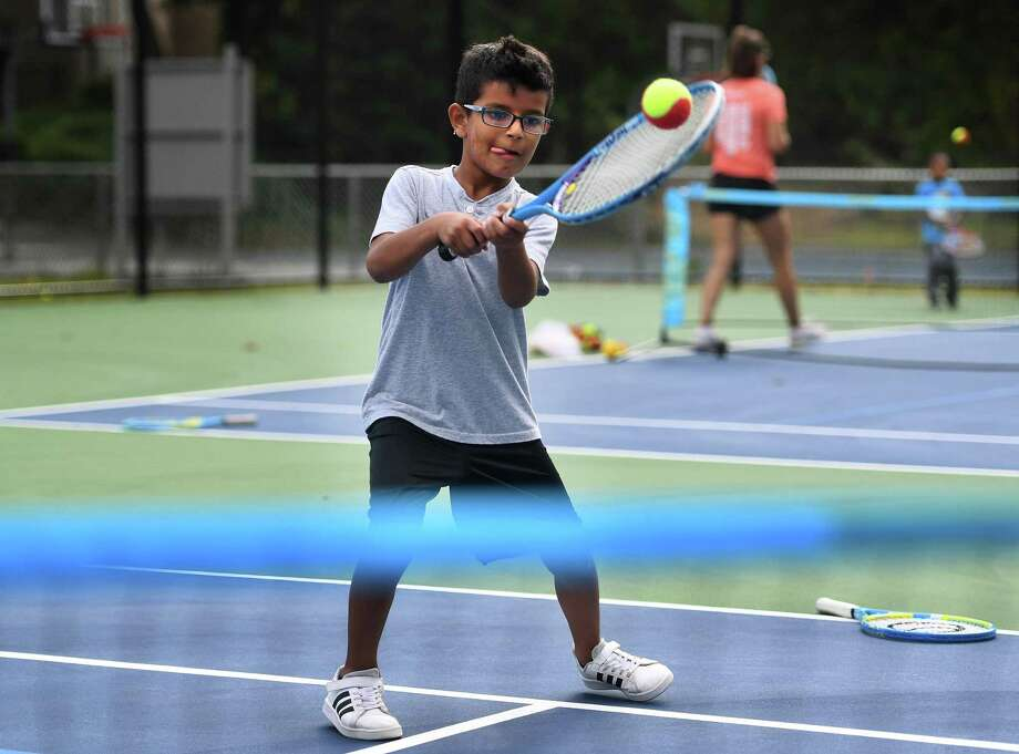 Thiago Marcelini, 8, of Norwalk, practices tennis with an instructor during the grand opening of the William Rippe Tennis Center at Norwalk Grassroots Tennis & Education at 11 Ingalls Avenue on Monday, September 9, 2019. Photo: Brian Pounds / Hearst Connecticut Media / Connecticut Post