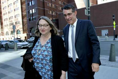 Michael Center, right, former men's tennis coach at the University of Texas at Austin, departs federal court with an unidentified woman, Wednesday, April 24, 2019, in Boston, after he plead guilty to charges in a nationwide college admissions bribery scandal.
