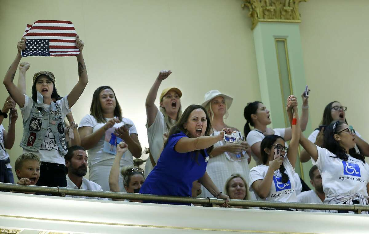 Opponents of recently passed legislation to tighten the rules on giving exemptions for vaccinations, demonstrate in the Assembly gallery after lawmakers approved the companion bill, at the Capitol in Sacramento, Calif., Monday, Sept. 9, 2019. The companion measure contained changes demanded by Gov Gavin Newsom as a condition of signing the controversial vaccine bill SB276 which was passed by the Legislature last week.(AP Photo/Rich Pedroncelli)