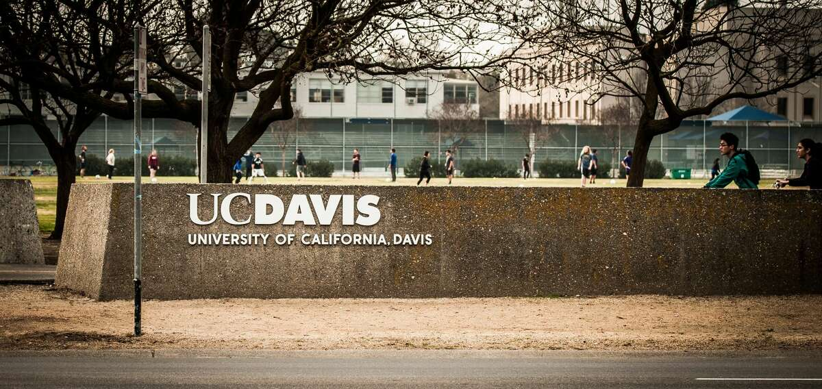 The UC Davis logo with a soccer game and bike riders in the background.