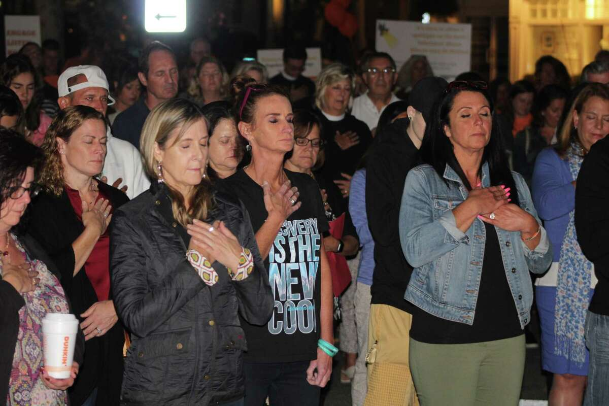 Members of the audience at the third annual Addiction Awareness Vigil in New Canaan on Thursday, Sept. 5, join in a group centering exercise.
