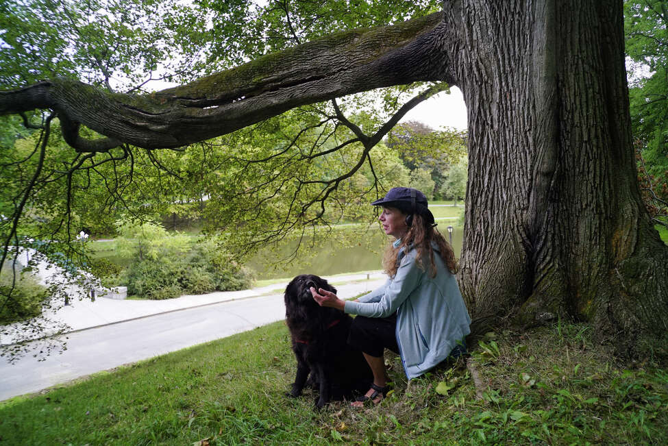 Jenna Barone feeds her service dog, Shadow Bear, some treats as the two sit on a hill in Washington Park on Monday, Sept. 9, 2019, in Albany, N.Y. (Paul Buckowski/Times)