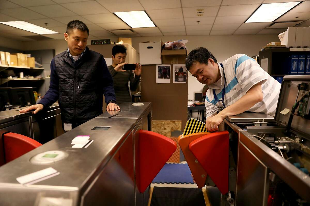 John Yen (left), manager for fare collection engineering, and Seung Lee, digital media producer, observe Weldon Chen, senior computer systems engineer, as he displays a finned barrier in the Fare Collection Engineering Machinery Laboratory at BART headquarters in Oakland, Calif., on Tuesday, January 29, 2019. BART is testing new, sturdier fare gates meant to ward off fare cheaters.