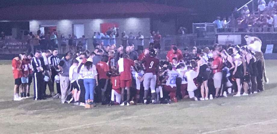 Players and coaches gather near midfield, praying and offering support to an injured Kirbyville player on Friday night at Wildcats Stadium. Facebook photo. Photo: Facebook Photo