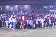 Players and coaches gather near midfield, praying and offering support to an injured Kirbyville player on Friday night at Wildcats Stadium. Facebook photo.