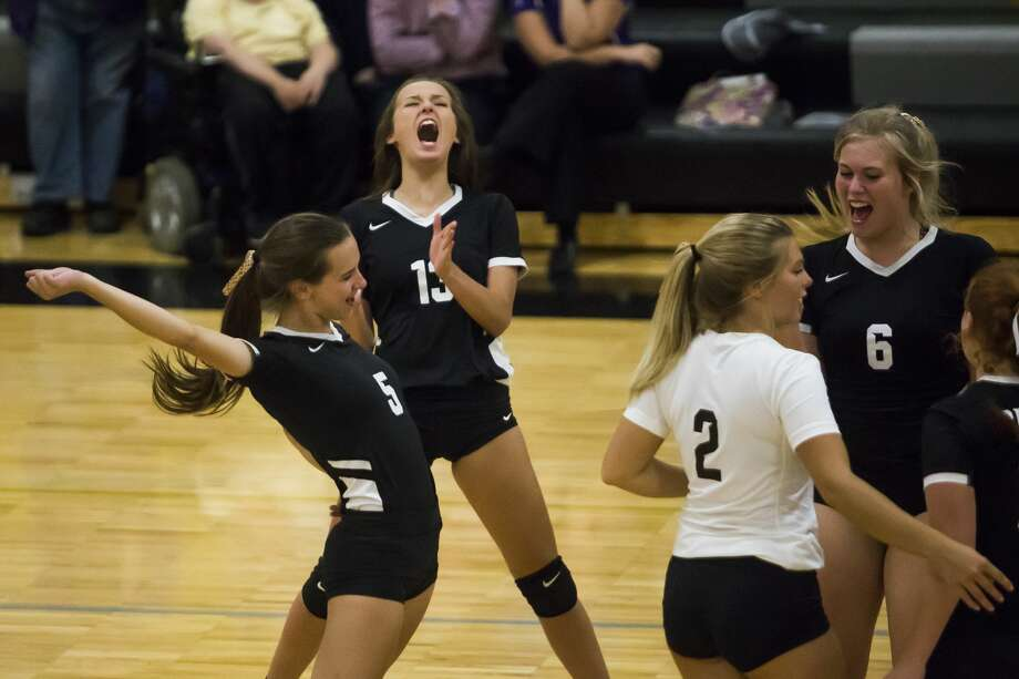 Bullock Creek's Kalli Nelson, center, and Courtney Niswander, left, cheer after their team scored the winning point during a match against Calvary Baptist Monday, Sept. 9, 2019 at Bullock Creek High School. (Katy Kildee/kkildee@mdn.net) Photo: (Katy Kildee/kkildee@mdn.net)
