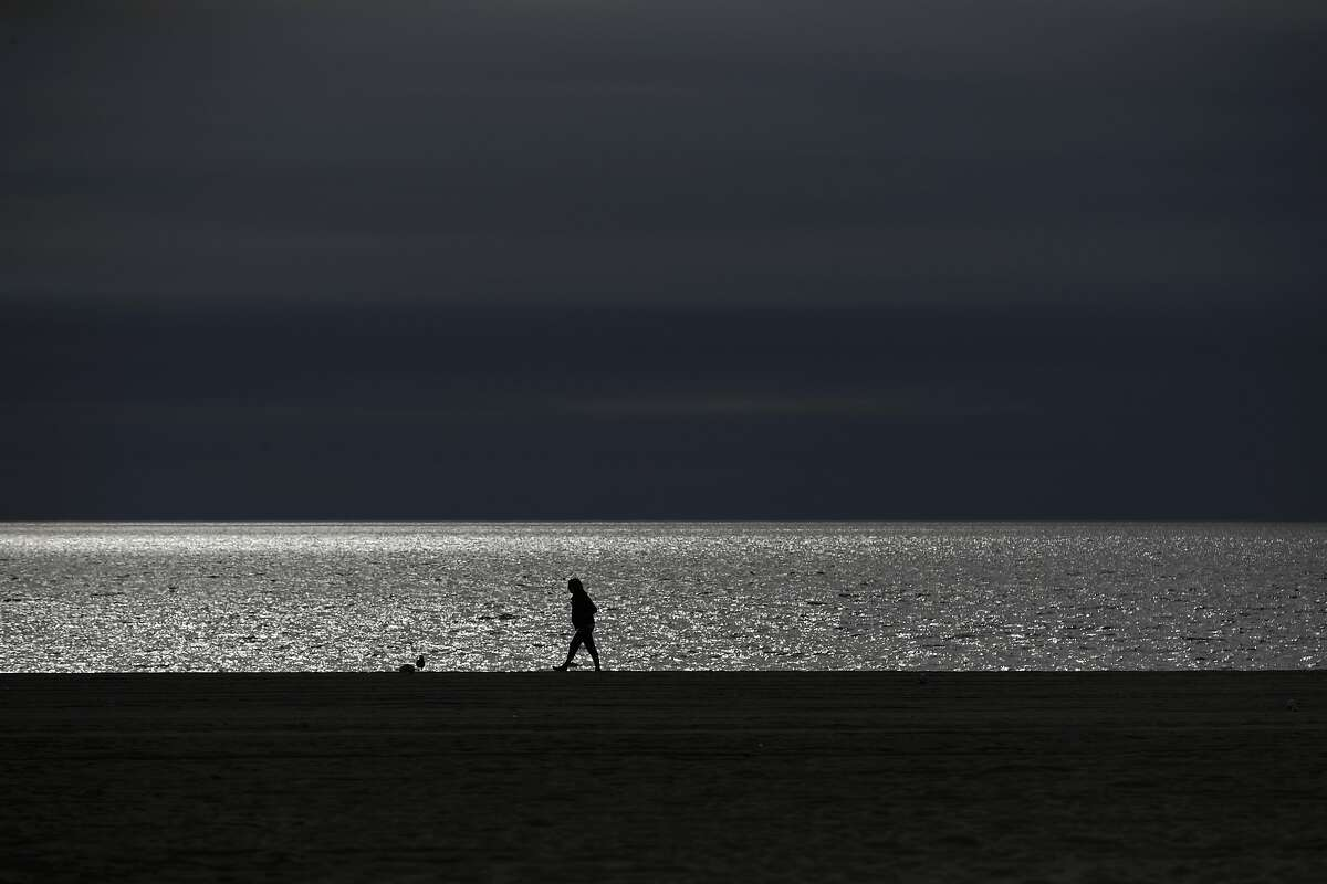 A person strolls along the beach as the Pacific Ocean glitters in the sun Wednesday, Feb. 27, 2019, in the Venice Beach section of Los Angeles. (AP Photo/Jae C. Hong)