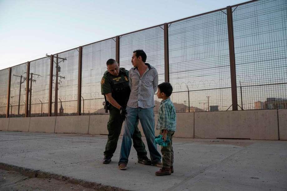 ARCHIVO— En esta foto tomada el 16 de mayo de 2019, el agente de la Oficina de Aduanas y Protección Fronteriza Frank Pino, registra a José, de 27 años, con su hijo José Daniel, de 6 años, en El Paso, Texas. Photo: PAUL RATJE /AFP /Getty Images / AFP or licensors