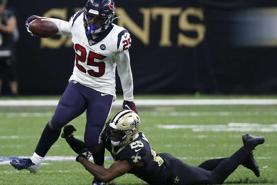 Houston Texans running back Duke Johnson (25) is tripped up by New Orleans Saints cornerback Eli Apple during the fourth quarter of an NFL football game at the Mercedes-Benz Superdome on Monday, Sept. 9, 2019, in New Orleans.