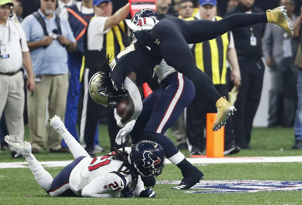 Houston Texans cornerback Bradley Roby (21) trips up New Orleans Saints running back Alvin Kamara (41) during the first quarter of an NFL football game at the Mercedes-Benz Superdome on Monday, Sept. 9, 2019, in New Orleans.