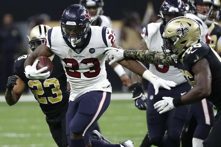 Houston Texans running back Carlos Hyde (23) runs the ball against New Orleans Saints outside linebacker Demario Davis (56) during the fourth quarter of an NFL  football game at the Mercedes-Benz Superdome on Monday, Sept. 9, 2019, in New Orleans.