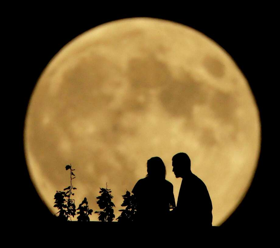 "A couple sits on a bluff overlooking the Missouri River as the full moon rises in the distance Monday, Sept. 8, 2014, in Kansas City, Mo. Monday night's full moon, also known as a Harvest Moon, will be the third and final ""supermoon"" of 2014. The phenomenon, which scientists call a ""perigee moon,"" occurs when the moon is near the horizon and appears larger and brighter than other full moons. (AP Photo/Charlie Riedel) Photo: Charlie Riedel / Associated Press / AP"