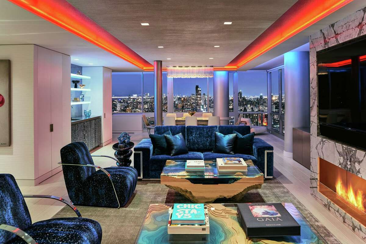 The living room of this New York City apartment, which shares the same magnificent views of the Manhattan skyline as the home's dining room in the background features a 75
