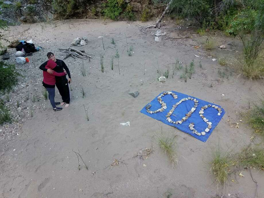 Krystal Ramirez and Hunter Whitson embrace after creating an SOS message out of rocks. Photo: Courtesy Of Curtis Whitson. / Handout